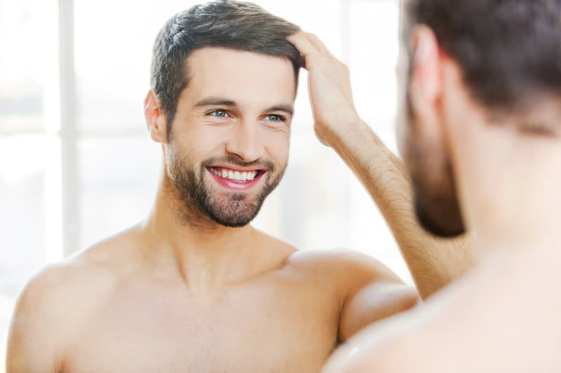 Man Admiring Successful Hair Transplant